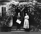 Lawrence.  Mr. and Mrs. C.W. Lawrence under rose arbor.